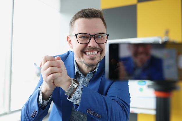 Młody zadowolony trener biznesu, zaciskając dłonie w pięści przed telefonem komórkowym