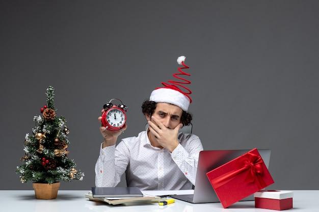 Młody zainteresowany biznesmen z czapką świętego mikołaja i trzymając zegar i myśląc o czymś w biurze na ciemnym tle
