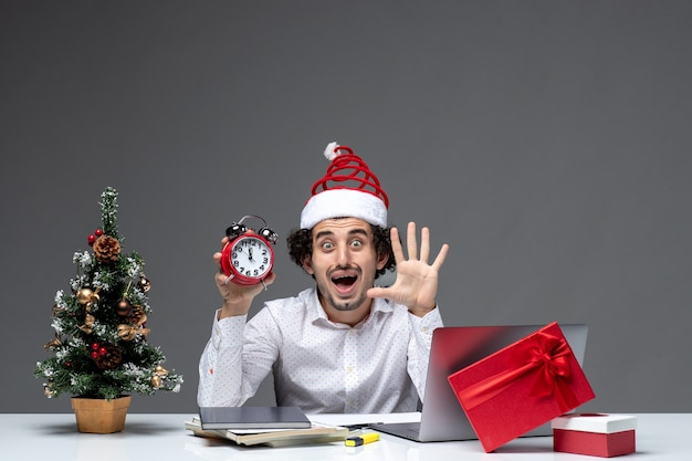Młody zainteresowany zaskoczony biznesmen z czapką świętego mikołaja i trzymając zegar i pokazując pięć w biurze na ciemnym tle