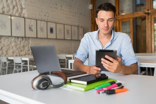 Młody, zajęty, zajęty człowiek skoncentrowany na pracy przy laptopie