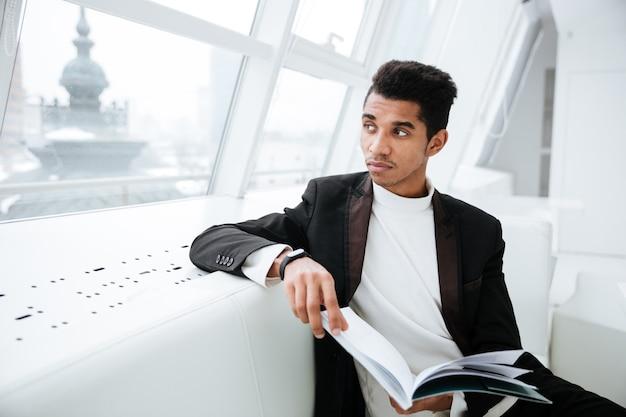 Młody zamyślony afrykański biznesowy mężczyzna w czarnym garniturze, siedzący na białej kanapie i trzymający dziennik w biurze
