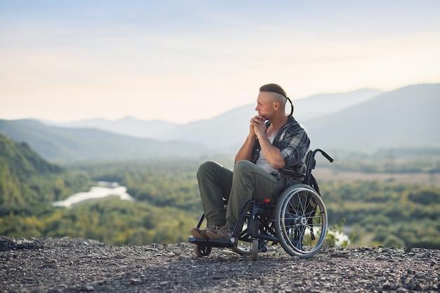 Młody zamyślony mężczyzna na wózku inwalidzkim, ciesząc się pięknem przyrody w górach. rehabilitacja po kontuzji.