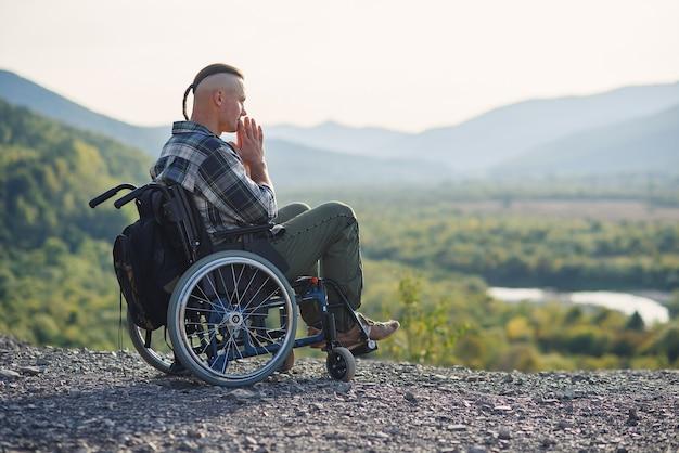 Młody zamyślony mężczyzna na wózku inwalidzkim, ciesząc się pięknem przyrody w górach