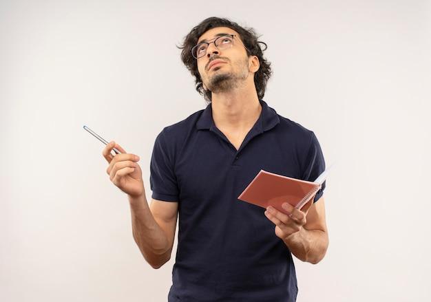 Młody zamyślony mężczyzna w czarnej koszuli z okularami optycznymi trzyma długopis i notatnik na białym tle na białej ścianie
