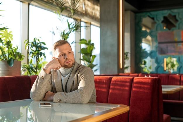 Młody zamyślony mężczyzna w kurtce i swetrze siedzi na kanapie z czerwonego aksamitu przy stole w eleganckiej restauracji i czeka na swoją dziewczynę