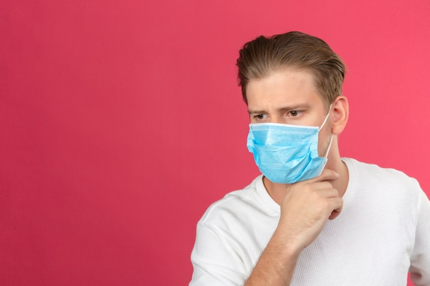 Młody zamyślony mężczyzna w medycznej masce ochronnej odwracając wzrok i trzymając rękę na brodzie, stojąc na na białym tle różowym tle