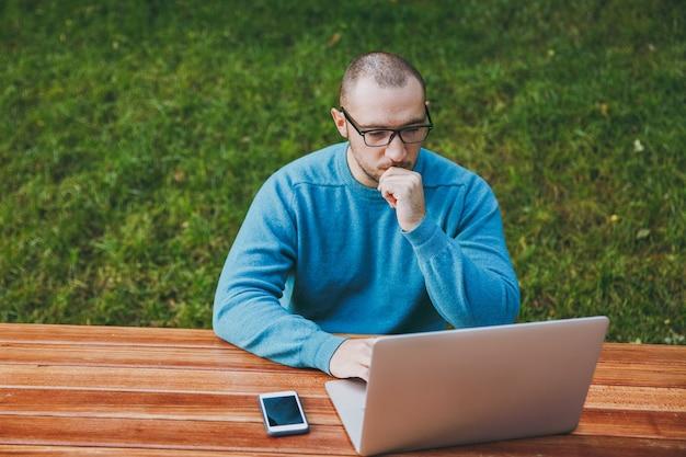 Młody zamyślony udany inteligentny człowiek biznesmen lub student w dorywczo niebieska koszula, okulary siedzi przy stole z telefonem komórkowym w parku miejskim za pomocą laptopa, pracując na naturze na zewnątrz. koncepcja mobilnego biura.