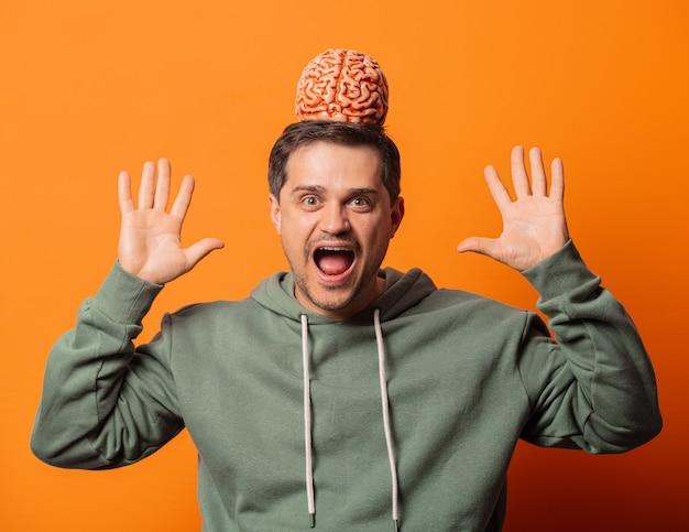 Młody zaskakujący facet z mózgiem na pomarańczowo