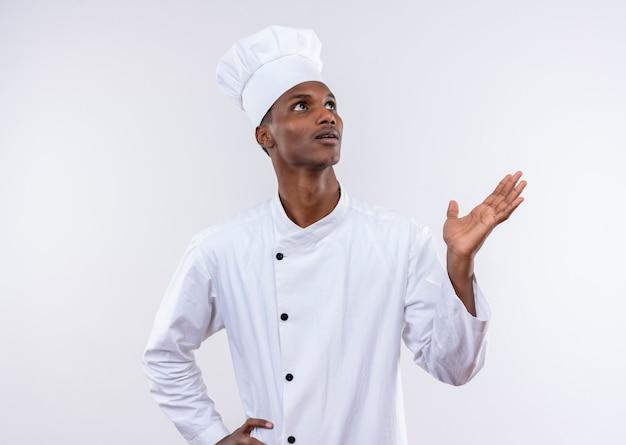 Młody zaskoczony afro-amerykański kucharz w mundurze szefa kuchni i wyszukuje na białym tle na białej ścianie