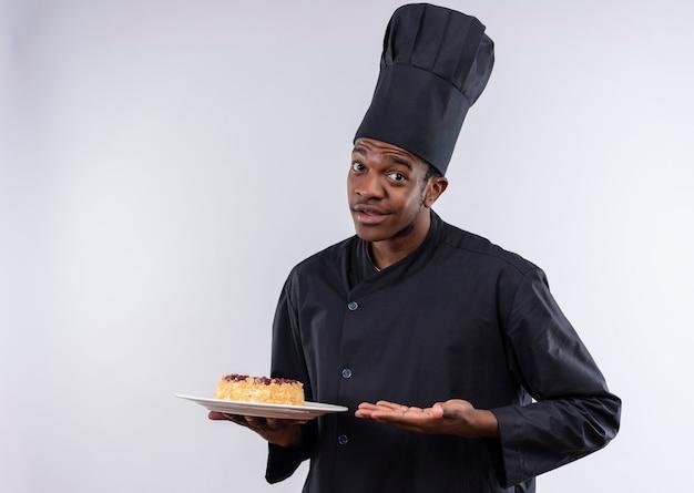 Młody zaskoczony afro-amerykański kucharz w mundurze szefa kuchni trzyma ciasto na talerzu i wskazuje ręką na białej ścianie
