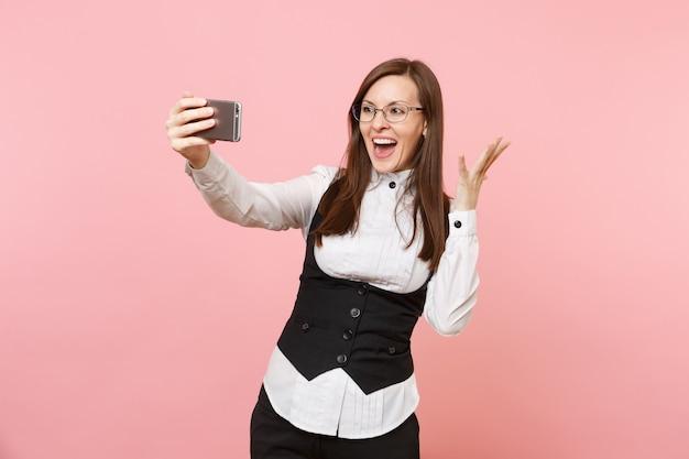 Młody zaskoczony biznes kobieta w okularach robi biorąc selfie strzał na telefon komórkowy rozkładając ręce na białym tle na różowym tle. szefowa. osiągnięcie bogactwa kariery. skopiuj miejsce na reklamę.