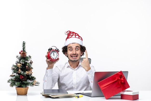 Młody zaskoczony biznesmen z czapką świętego mikołaja i trzymając zegar i pokazując jeden w biurze na białym tle