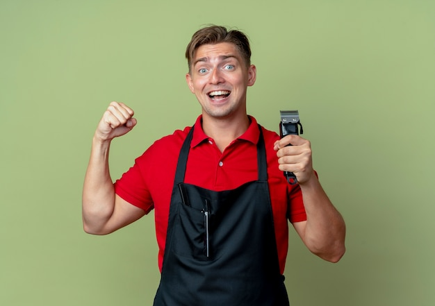 Młody zaskoczony blond mężczyzna fryzjer w mundurze trzyma maszynkę do strzyżenia włosów i podnosi pięść na tle oliwkowej przestrzeni z miejsca na kopię