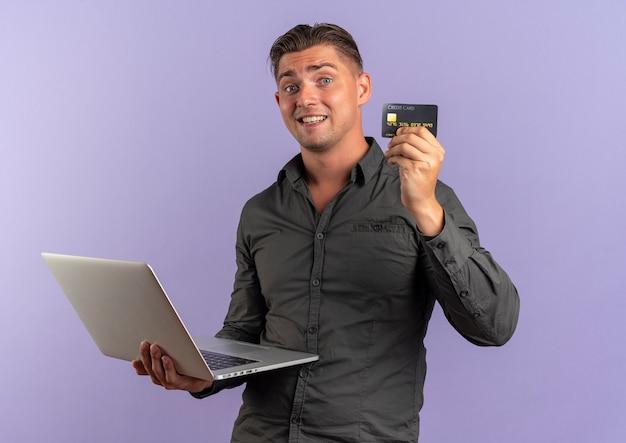 Młody zaskoczony blondynka przystojny mężczyzna trzyma laptopa i kartę kredytową
