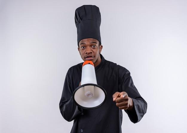 Młody zaskoczony kucharz afro-amerykański w mundurze szefa kuchni trzyma głośnik na białym tle na białej ścianie
