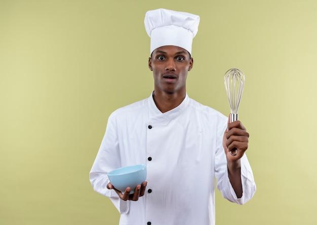 Młody zaskoczony kucharz afro-amerykański w mundurze szefa kuchni trzyma miskę i trzepaczkę na białym tle na zielonej ścianie