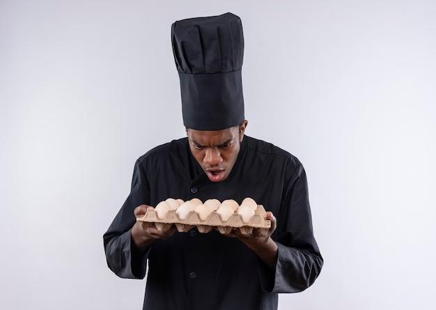 Młody zaskoczony kucharz afro-amerykański w mundurze szefa kuchni trzyma partię jaj na białym tle na białej ścianie