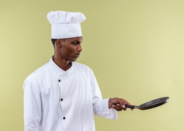Młody zaskoczony kucharz afro-amerykański w mundurze szefa kuchni trzyma patelnię na białym tle na zielonej ścianie