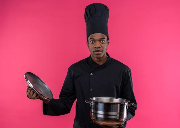 Młody zaskoczony kucharz afro-amerykański w mundurze szefa kuchni trzyma rondel na białym tle na różowej ścianie