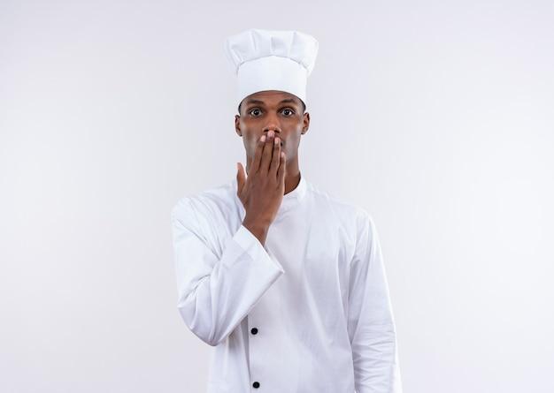 Młody zaskoczony kucharz afroamerykański w mundurze szefa kuchni kładzie rękę na ustach na białej ścianie
