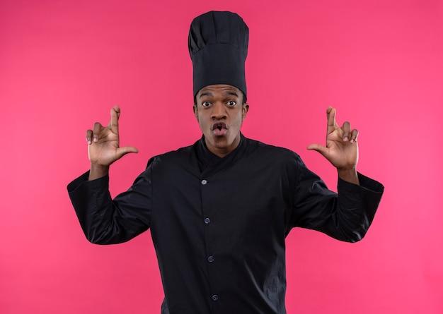 Młody zaskoczony kucharz afroamerykański w mundurze szefa kuchni krzyżuje palce obu rąk na różowej ścianie