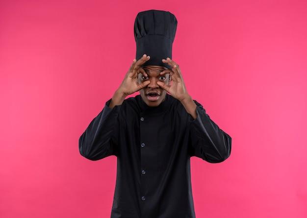 Młody zaskoczony kucharz afroamerykański w mundurze szefa kuchni otwiera oczy rękami odizolowanymi na różowej ścianie
