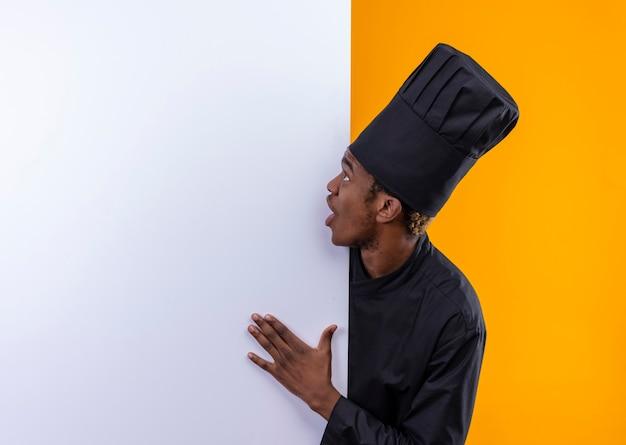 Młody zaskoczony kucharz afroamerykański w mundurze szefa kuchni stoi za białą ścianą i patrzy na ścianę odizolowaną na pomarańczowej ścianie