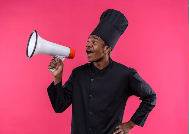 Młody zaskoczony kucharz afroamerykański w mundurze szefa kuchni trzyma głośnik na różowej ścianie