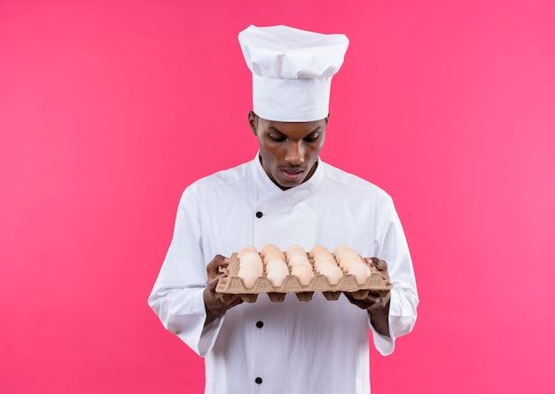 Młody zaskoczony kucharz afroamerykański w mundurze szefa kuchni trzyma i patrzy na partię świeżych jaj na białym tle na różowej ścianie
