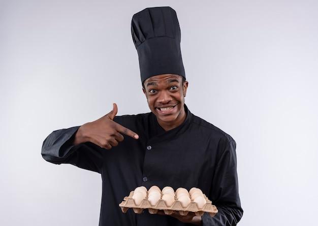 Młody zaskoczony kucharz afroamerykański w mundurze szefa kuchni trzyma i wskazuje na partię jaj na białej ścianie