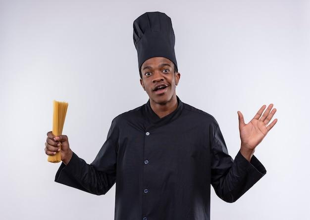 Młody zaskoczony kucharz afroamerykański w mundurze szefa kuchni trzyma kilka spaghetti i trzyma rękę na białym tle na białej ścianie