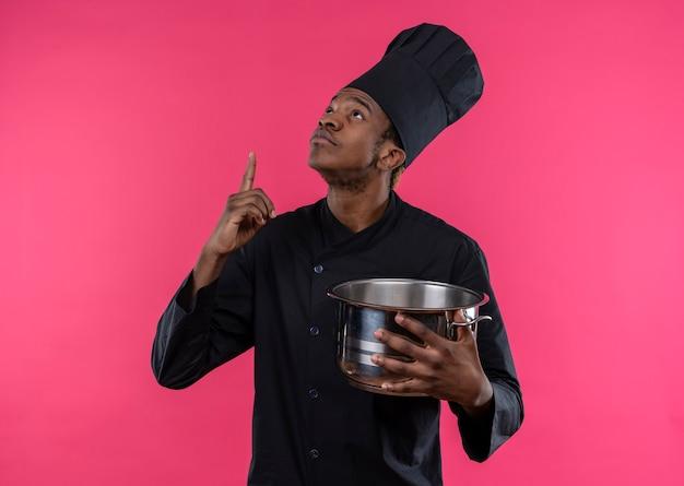 Młody zaskoczony kucharz afroamerykański w mundurze szefa kuchni trzyma rondel i wskazuje w górę na białym tle na różowej ścianie