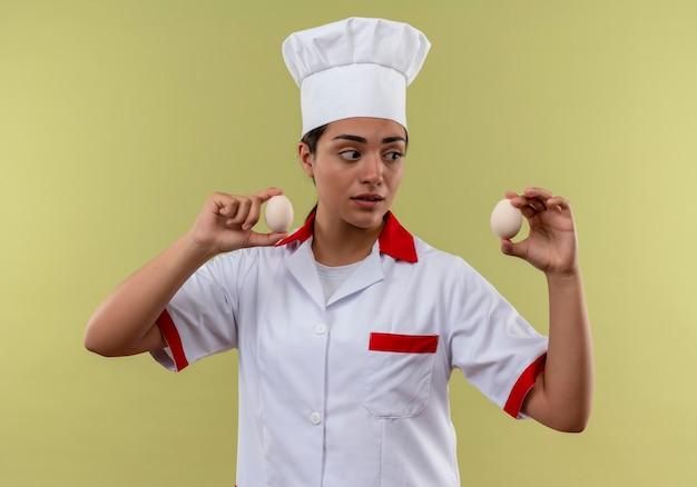 Młody zaskoczony kucharz kaukaski dziewczyna w mundurze szefa kuchni trzyma jajka na białym tle na zielonej ścianie z miejsca na kopię