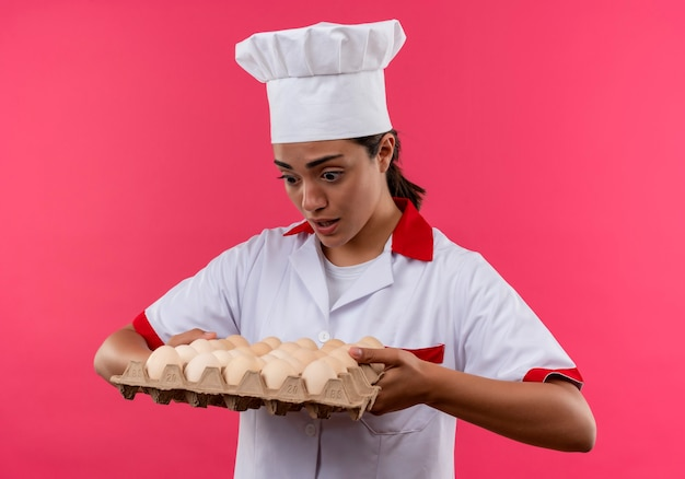 Młody zaskoczony kucharz kaukaski dziewczyna w mundurze szefa kuchni trzyma partię jaj na białym tle na różowej ścianie z miejsca na kopię
