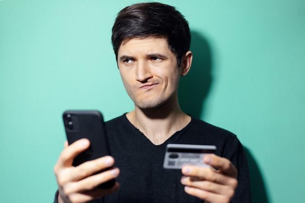 Młody zaskoczony mężczyzna ze smartfonem i kartą kredytową w ręku na ścianie w kolorze aqua menthe.