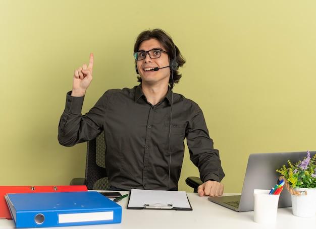 Młody zaskoczony pracownik biurowy mężczyzna na słuchawkach w okularach optycznych siedzi przy biurku z narzędziami biurowymi za pomocą laptopa skierowanego w górę, patrząc na bok na białym tle na zielonym tle z przestrzenią do kopiowania