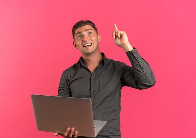 Młody zaskoczony przystojny blondyn trzyma laptopa i wskazuje patrząc w górę
