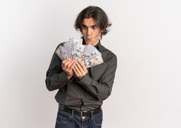 Młody zaskoczony przystojny kaukaski mężczyzna trzyma i patrzy na pieniądze na białym tle na białym tle z miejsca na kopię