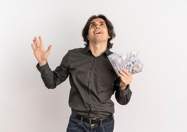 Młody zaskoczony przystojny kaukaski mężczyzna trzyma pieniądze i patrzy w górę na białym tle na białym tle z miejsca na kopię