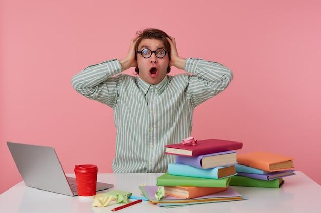 Młody zaskoczony student w okularach, siedzi przy stole i pracuje z laptopem, zakrywa uszy i krzyczy, odizolowane na różowym tle.