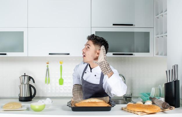Młody zaskoczony szef kuchni w mundurze noszącym uchwyt i świeżo upieczony chleb na stole