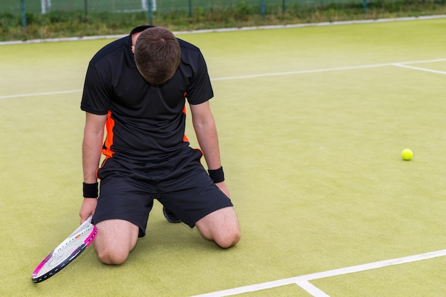 Młody zawodnik ubrany w strój sportowy jest zdenerwowany i upadł na kolana z powodu przegranego meczu tenisowego na korcie