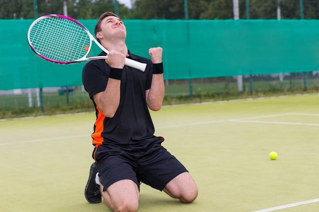 Młody zawodnik upadł na kolana i zacisnął pięść z powodu wygranej w meczu na korcie tenisowym