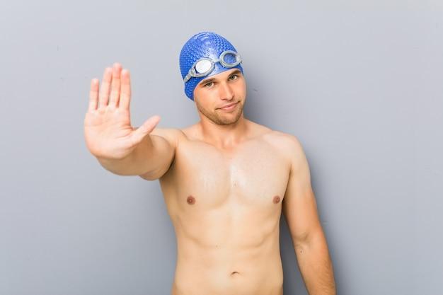 Młody zawodowy pływak mężczyzna stojący z wyciągniętą ręką pokazujący znak stopu, uniemożliwiając ci.