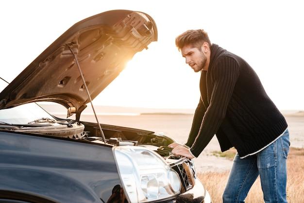 Młody zdenerwowany przypadkowy mężczyzna próbujący naprawić swój zepsuty samochód na zewnątrz
