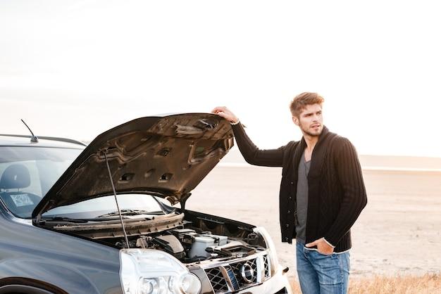 Młody zdenerwowany przypadkowy mężczyzna stojący przy swoim zepsutym samochodzie na zewnątrz