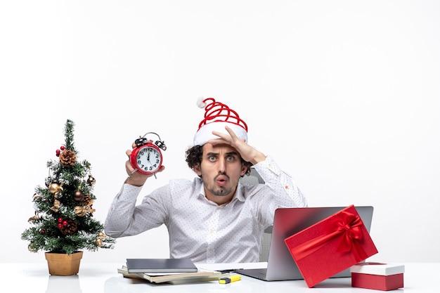Młody zdezorientowany biznesmen z czapką świętego mikołaja i pokazując zegar i burzę mózgów, siedząc w biurze na białym tle