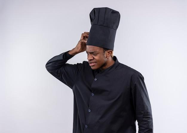 Młody zdezorientowany kucharz afro-amerykański w mundurze szefa kuchni kładzie rękę na głowie na białym tle na białej ścianie