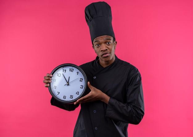 Młody zdezorientowany kucharz afro-amerykański w mundurze szefa kuchni trzyma zegar na białym tle na różowej ścianie