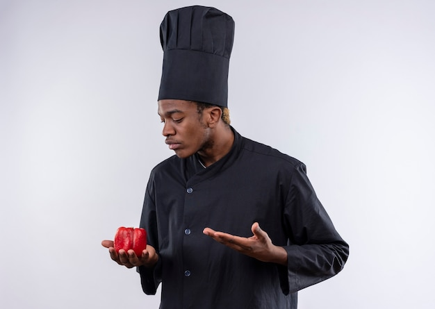 Młody zdezorientowany kucharz afroamerykański w mundurze szefa kuchni trzyma czerwoną paprykę i wskazuje ręką na białej ścianie